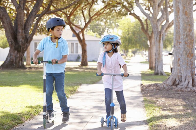 boy and girl riding scooters